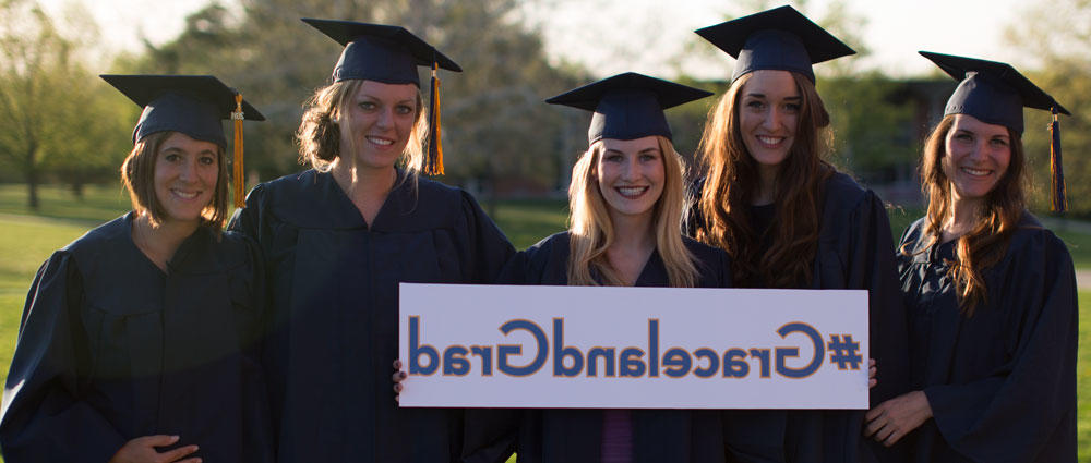 Three female graduates in cap and gown holding a sign: #GracelandGrad